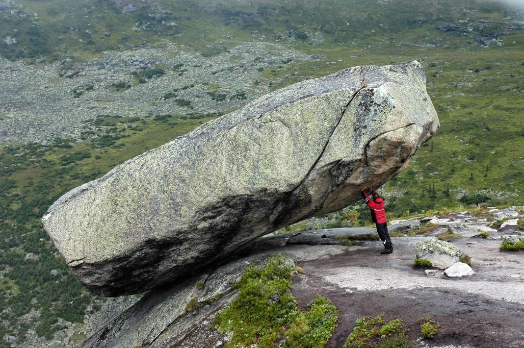 Челоек поднимает огромный камень